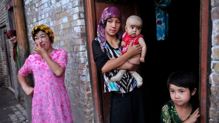 An ethnic Uighur woman hugs her son as she stands outside her house with her daughter and neighbors