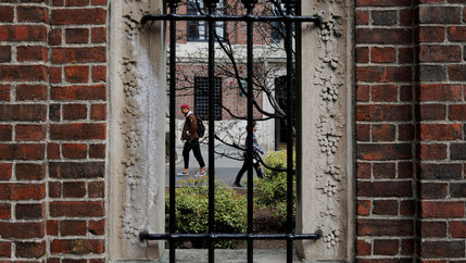 Several people are shown through a stone window with metal bars on it walking.
