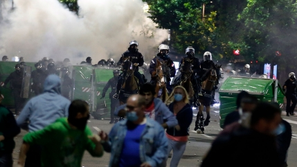 A large group of people are shown running from police officers on horseback with smoke in the distance.