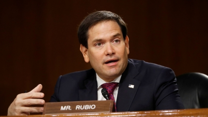 US Sen. Marco Rubio is shown wearing a dark suit and speaking with a small placard in front of him with his name on it.