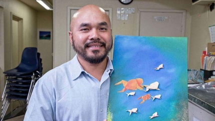 Chanthon Bun, who was incarcerated for 23 years, part of that time in San Quentin State Prison in California, shows artwork from an origami course offered in the prison.