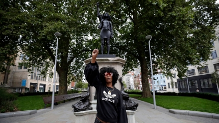 A woman wearing a dark jacket and sunglasses is shown standing in front of a statue of her with her hand raised.