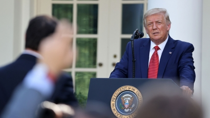 US President Donald Trump is shown standing at a podium and wearing a blue suit and red tie.