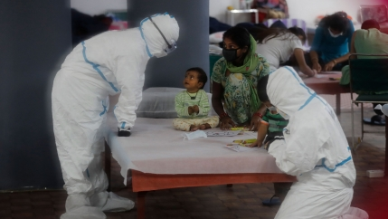 A young child is shown sitting on a bed with health care workers nearby dressed in full protective suits.