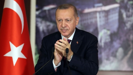 Turkey's President Recep Tayyip Erdoğan is shown wearing a dark suit and standing behind a microphone with a Turkish flag nearby.