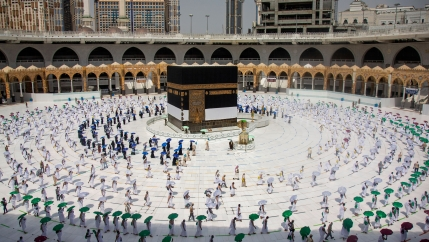 Pilgrims are shown from above around the cube-like Kaaba in Mecca walking on specified lines and carrying colored umbrellas.