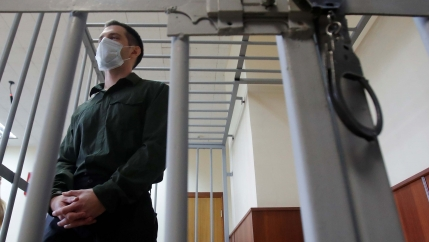 Former US Marine Trevor Reed, who was detained in 2019 and accused of assaulting police officers, stands inside a defendants' cage during a court hearing in Moscow, Russia July 30, 2020.
