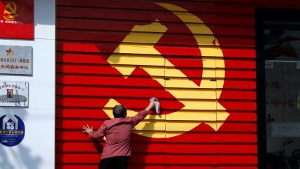 A person washes a wall with painted big yellow hammer and sickle of the Chinese Communist Party.