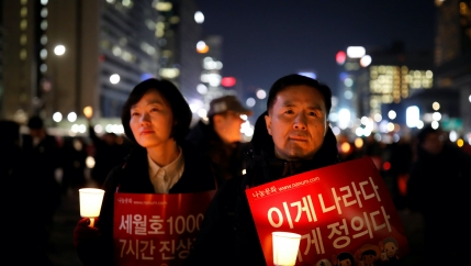 A woman and a man hold signs and candles lit up in the dark outside