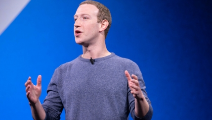 Mark Zuckerberg stands in front of a blue backdrop and speaks on climate misinformation using his hands