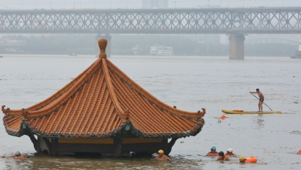 People swim near a partially flooded pavilion near banks of Yangtze River
