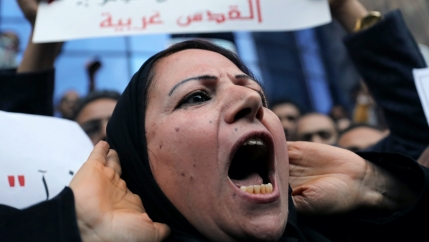 A woman shouts at a protest near a sign with red Arabic script