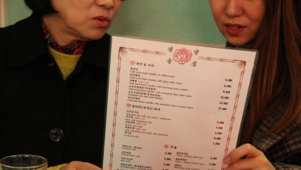 Han (left), a North Korean defector who asked that her full name not be used, and Kim Eun-joo (right) hold a menu together while examining the selection of North Korean dishes offered by the pub.