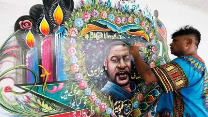 Pakistani truck-art painter Haider Ali, 40, touches up a mural depicting George Floyd in Karachi, Pakistan, June 12, 2020.
