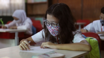 A young girl is shown sitting at a classroom desk wearing a protective face mask and plastic face guard while holding a pen.