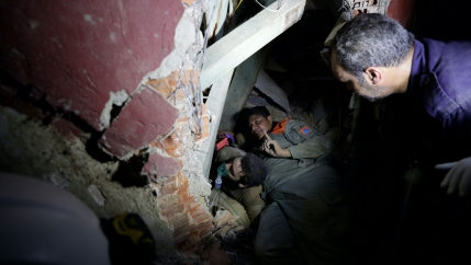 Several people are shown wearing military fatigues and digging through building rubble.