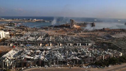 A photo showing Beirut's port left in complete rubble with smoke rising from parts and the Mediterranean Sea in the distance.