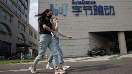 Two women are shown wearing jeans and face masks while walking past the ByteDance headquarters with large English and Chinese writing on the side.