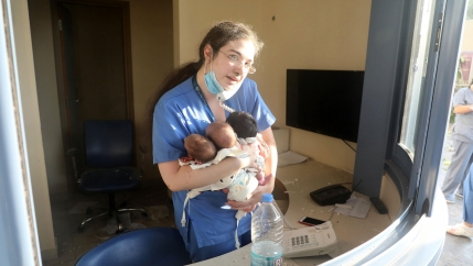 A woman with long hair and glasses wears blue scrubs holding three infants in her arms while talking on a phone in a damaged hospital