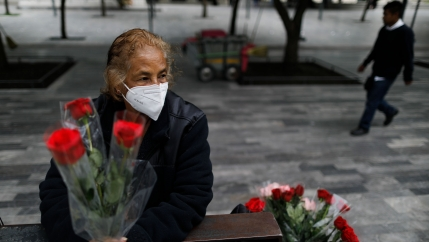 A woman is shown sitting on a metal bench and holding three red roses while wearing a protective face mask.