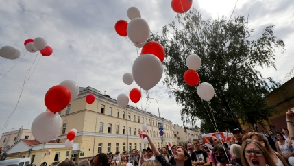 A large crowd of people are shown releasing red and white balloons into the air.