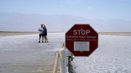 A sign the shape of a red stop sign warns of extreme heat danger at Badwater Basin with a couple taking a selfie in the distance.