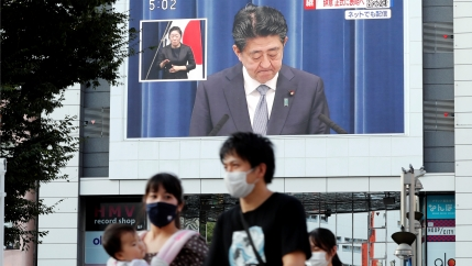 People walk past a large screen in Tokyo, Japan, broadcasting the news conference of Japanese Prime Minister Shinzo Abe where he announced his resignation.