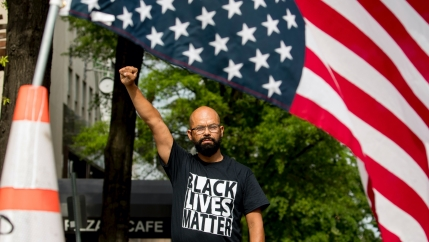A man raises his fist and wears a black BLM shirt as he stands in the sunroof of a car with a huge American flag.