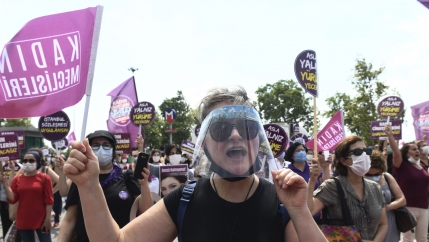 Women hold protest signs and also wear face masks and plastic shields as they protest.