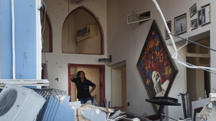 A woman stands inside a damaged interior with blue painted walls underneath an arch and art hung loosely on the walls.