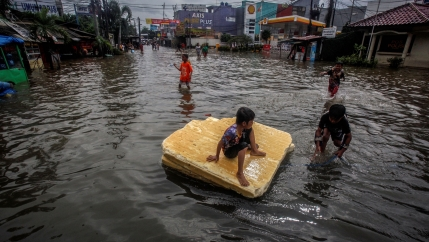 Children play in the floodwaters after heavy rains in Bekasi, near Jakarta, Indonesia, Feb. 25, 2020.
