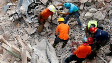 Lebanese and Chilean rescuers search at he site of a collapsed building after getting signals there may be a survivor under the rubble, in Beirut, Lebanon, Sept. 4, 2020.