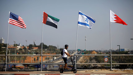 A man rides a scooter past the flags of the US, United Arab Emirates, Israel and Bahrain along a road in Netanya, Israel, Sept. 14, 2020.