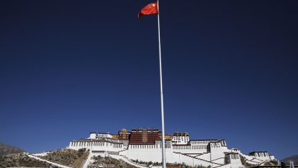China's red flag is show flying on a pole with the large white facade of the Potala Palace in the distance.