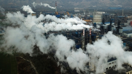 A large coal processing plant is shown from above with several smokestacks billowing emmissions.