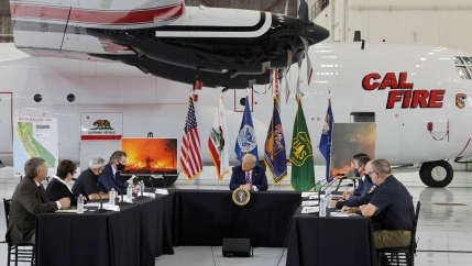US President Donald Trump sits in front of a CAL FIRE firefighting aircraft as California Governor Gavin Newsom speaks during a briefing on wildfires in McClellan Park, Calif., Sept. 14, 2020.