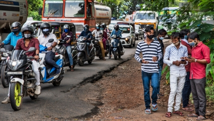 A street is shown lined with motorcyclists and work trucks with a group of five men standing nearby wearing face masks.