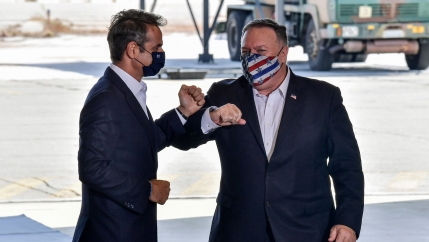 US Secretary of State Mike Pompeo, right, and Greek Prime Minister Kyriakos Mitsotakis are shown both wearing dark blazers and bumping elbows.