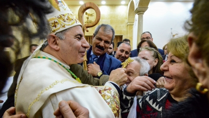 An archbishop blesses a man with his golden cross