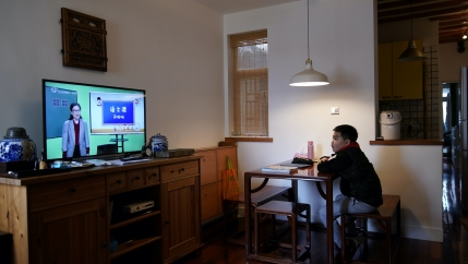 A boy sits in a living room at a desk and watches a TV with a lesson airing on it.