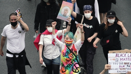 A group of protesters carries protest signs. One wears a colorful tie-dye shirt and has blue hair. The others wear white and black shirts.
