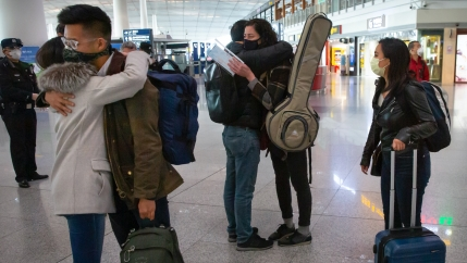 Pairs of individuals hug each other at an airport with their luggage on their shoulders and near their bodies