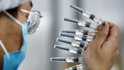 A man with glasses is shown in a close-up photo holding several syringes up to the light.