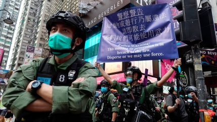 Security forces in Hong Kong are shown wearing face masks and helmets with one holding up a large purple warning banner.