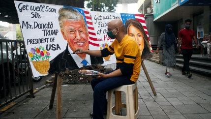 A man paints a mural of US President Donald Trump and First Lady Melania Trump after they tested positive for the coronavirus disease (COVID-19), on a street in Mumbai, India, Oct. 2, 2020.