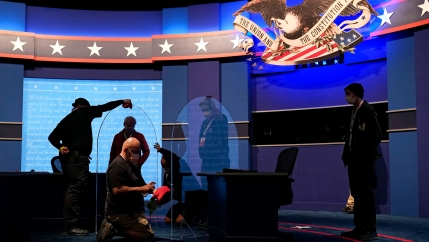 Workers clean protective plastic panels onstage between tables for Mike Pence and Kamala Harris with a large backdrop that includes stars across it.