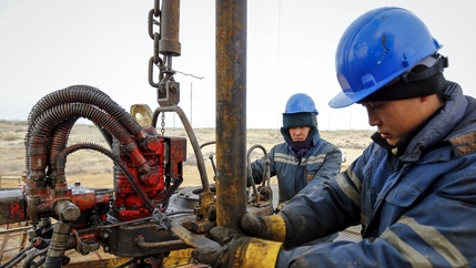 Two people wearing uniforms and blue helmets carry out maintenance at an oil well
