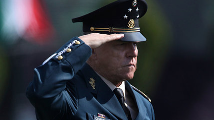 Mexico's Defense Secretary Gen. Salvador Cienfuegos Zepeda is shown wearing his military uniform and billed hat while holding his right hand up to salute.
