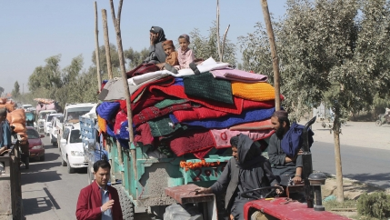 Afghan families leave their houses after fighting between the Afghan military and Taliban insurgents in Helmand province in southern Afghanistan, Oct. 13, 2020.