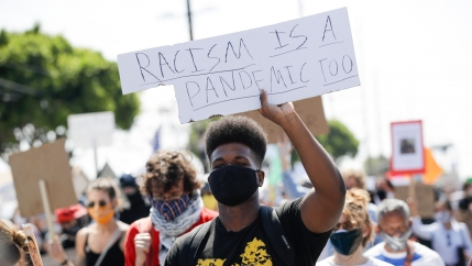 A crowd of protesters are shown with a man in the center holding a sign that reads,